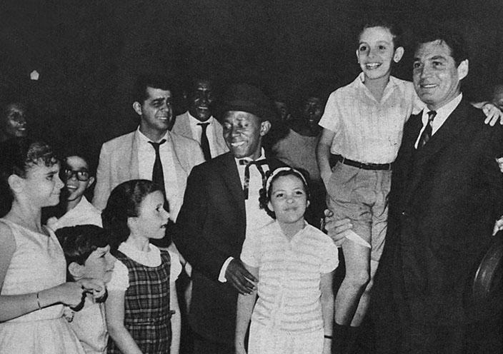 Gene Barry no aeroporto do Galão sendo recepcionado por uma multidão.